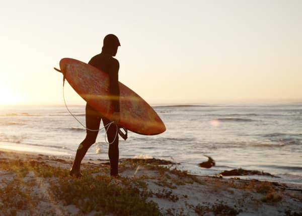 Surfer walking to ocean during video production in Cape Town.