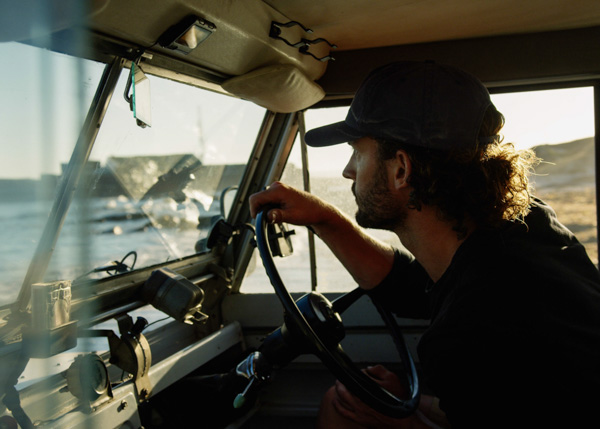 Man driving Land Rover during video production in Cape Town.