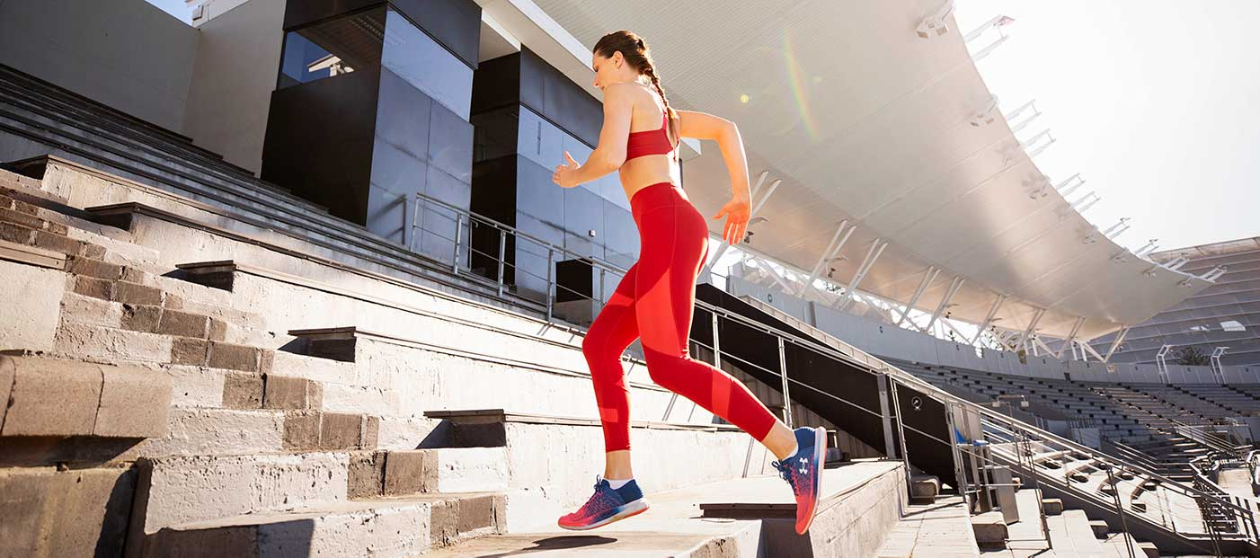 Woman in red Active wear running up stairs during photo production.